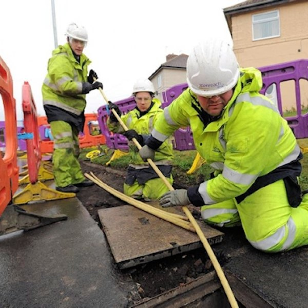 openreach engineers pulling fibre optic cable duct
