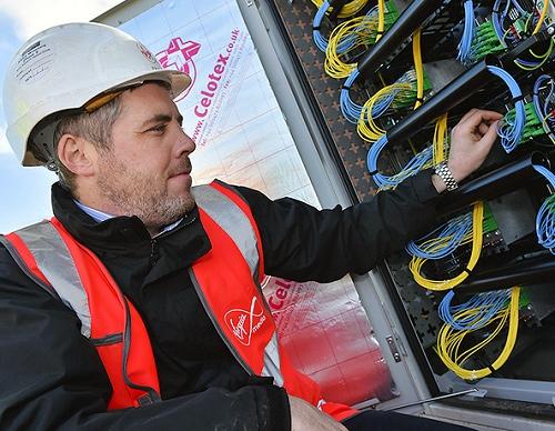 virgin media engineer touching fibre optic wires