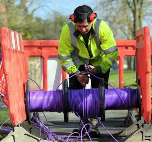 cityfibre engineer over reel of purple fibre