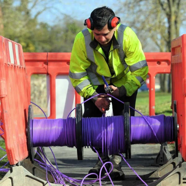 cityfibre engineer over reel of purple fibre