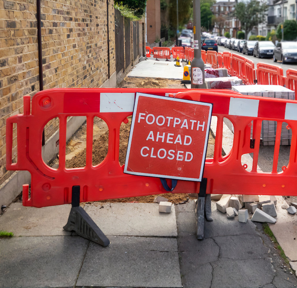 Works to lay new paving slabs and temporary footpath closed red warning sign on London sidewalk