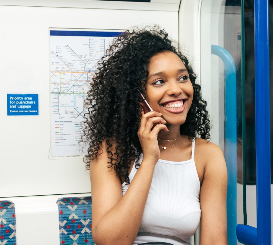 Young black woman sitting inside the underground on the mobile phone